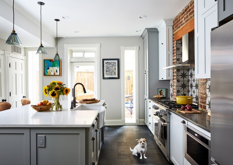 Island with farmhouse sink white cabinets with black knobs and back door leaving to the porch