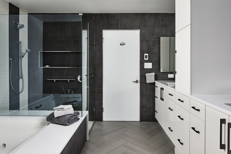 Large master bathroom with white cabinets and black handlers