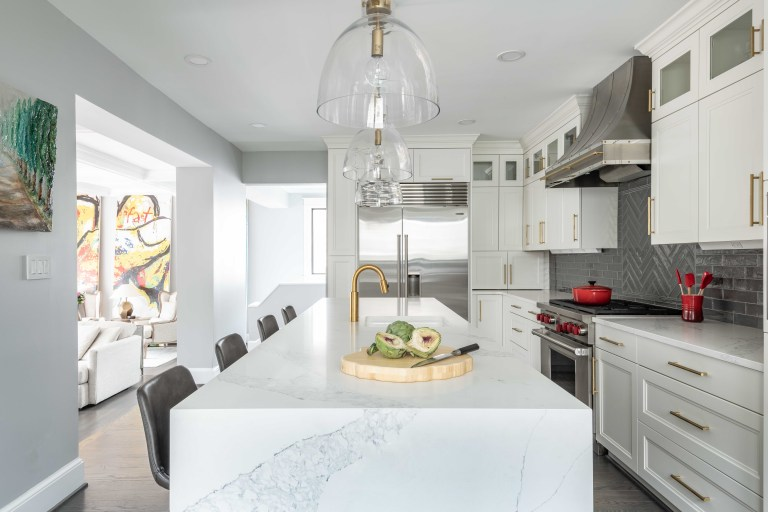 overview of kitchen white color palette with marble waterfall edge countertops on island