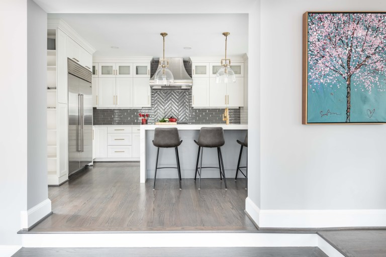 entryway into kitchen with wood floors white cabinets stainless steel appliances and large island with seating