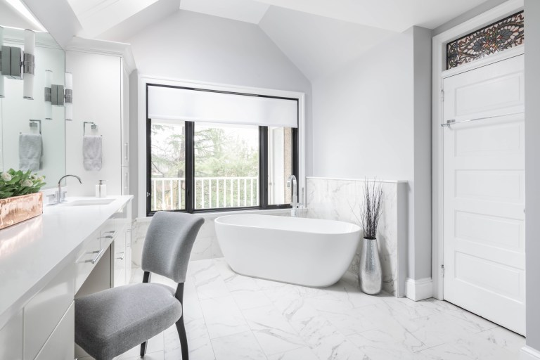freestanding tub under large window angled ceiling marble tiling stained glass window feature above door