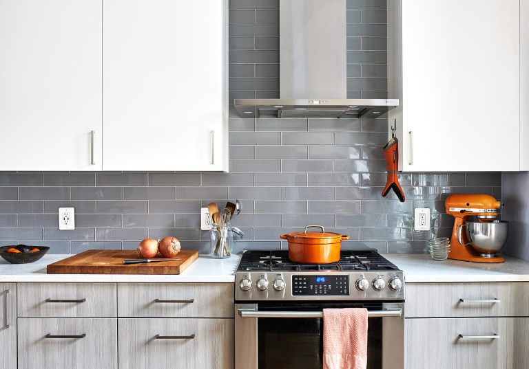 kitchen with gray subway tile backsplash stainless steel range and hood