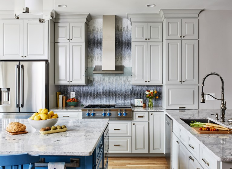kitchen with white cabinetry wood floors blue island mosaic backsplash stainless steel appliances