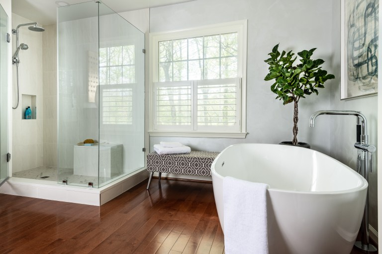 white large freestanding tub, hard wood floors, walk-in shower with rain shower head glass frameless doors with a window view