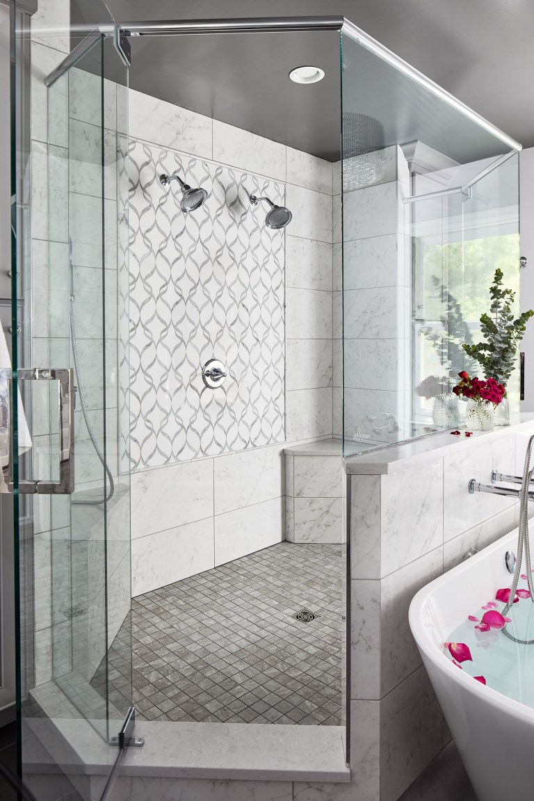 bathroom with large walk in shower with two shower heads