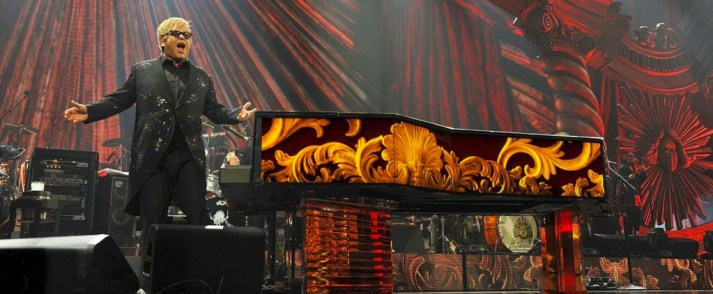 elton john performing next to a piano with flames down it in vegas
