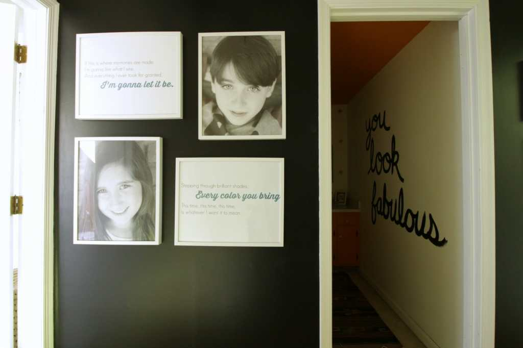 Black and white photo gallery wall in hallway.