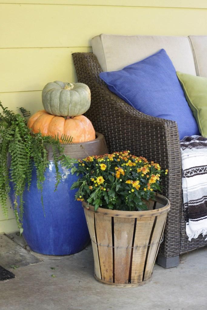 Pumpkins stacked in planter urns, bushel baskets with mums