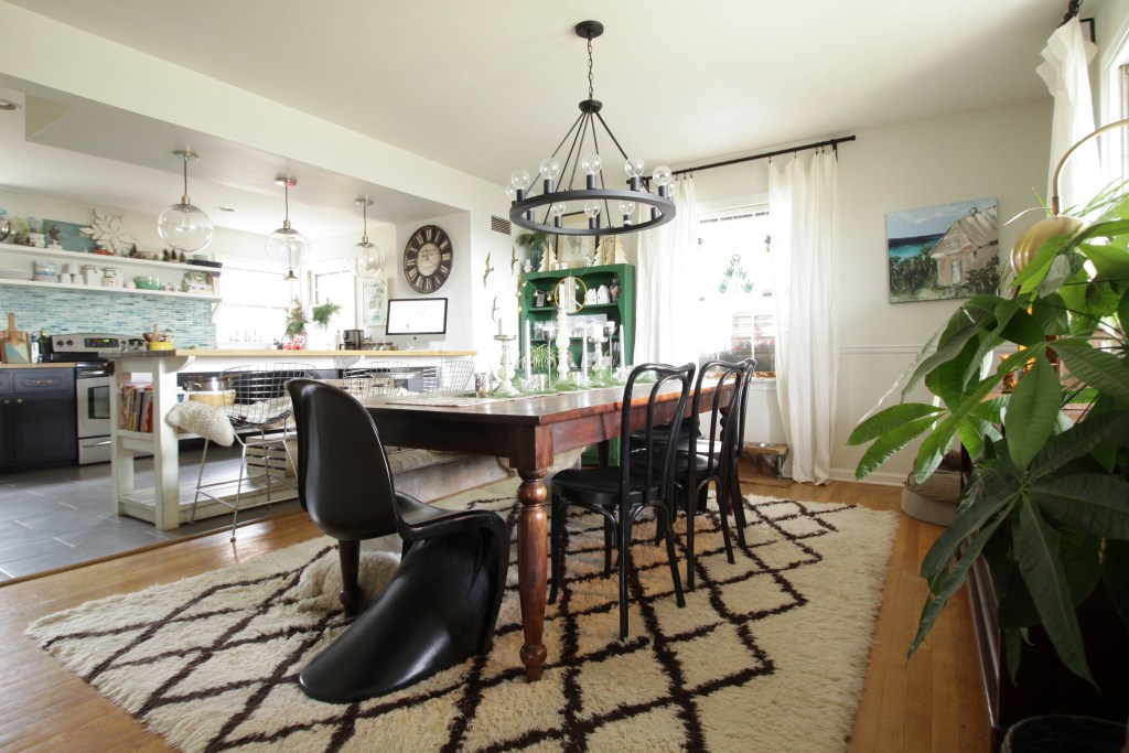 Eclectic open dining and kitchen space with industrial island