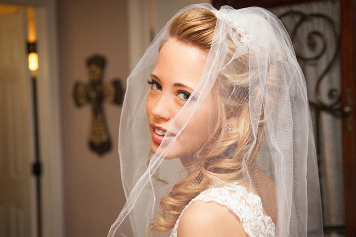 Bride through veil with cross