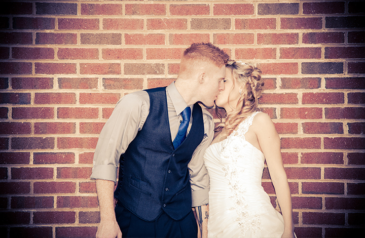 bride-and-groom-kiss-brick-wall