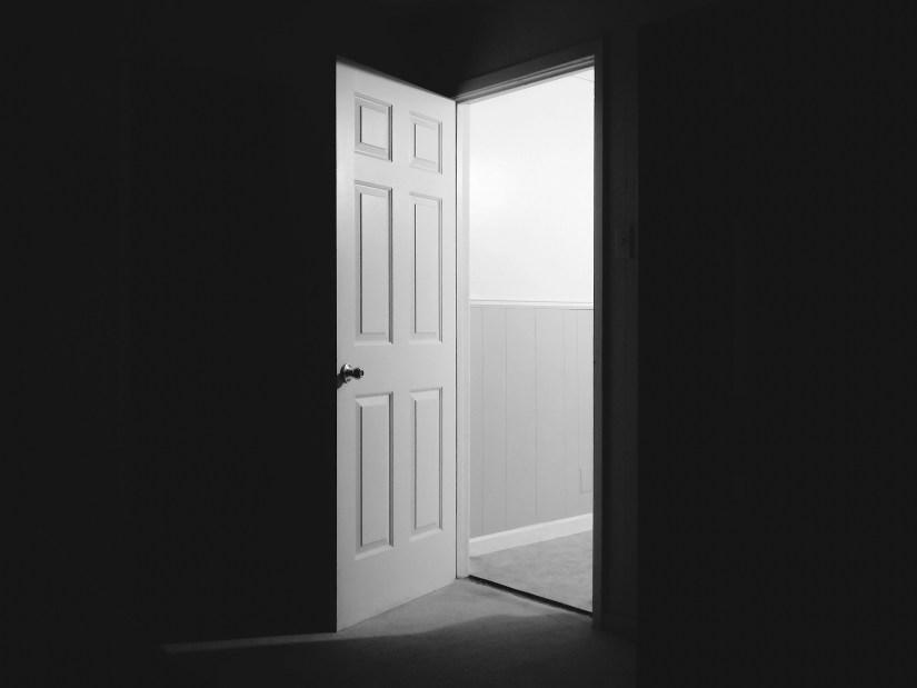 An open door in a hallway at night.