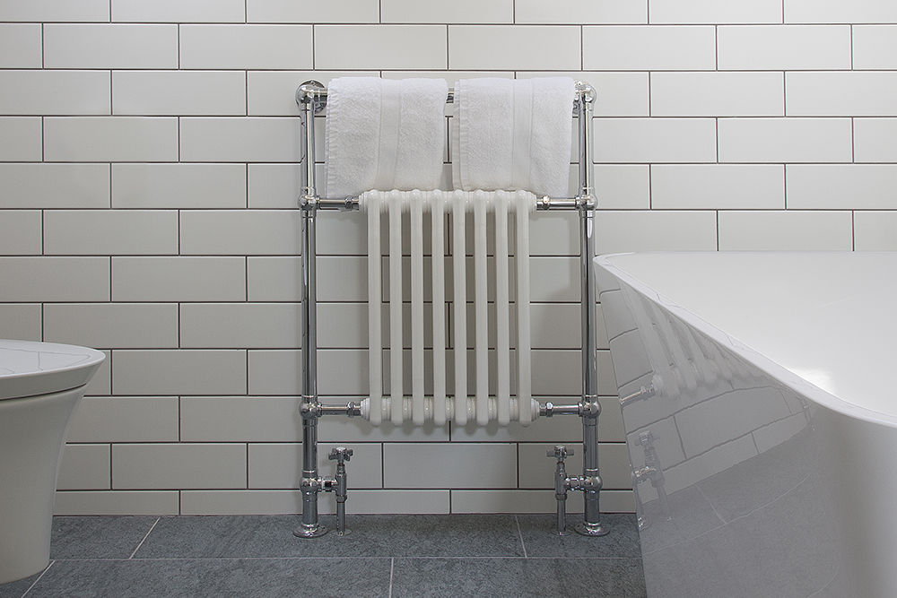 Traditional towel radiator in white tiled bathroom
