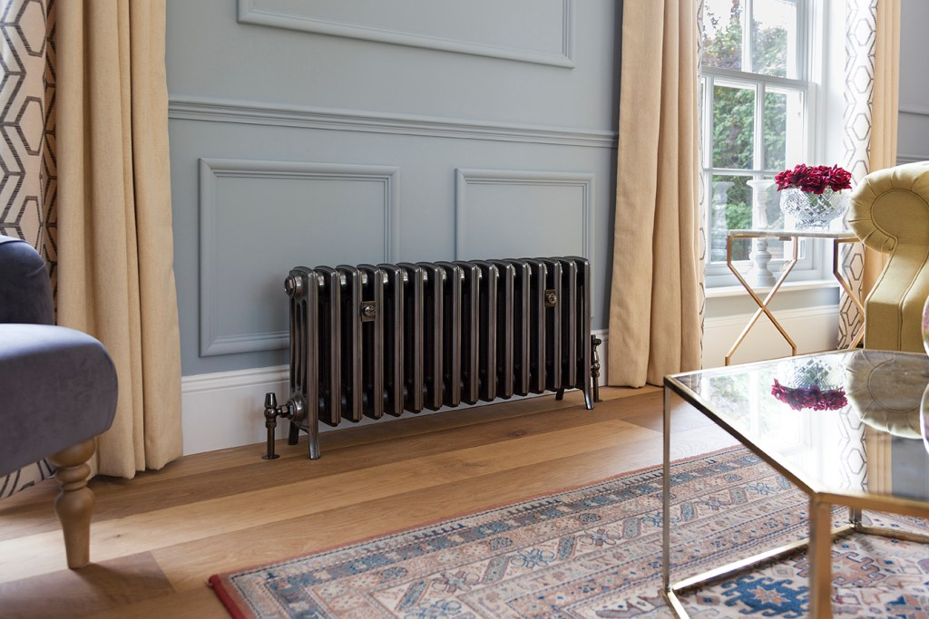 Full polish 4 column cast iron radiator infront of blue wall panelling and wooden floor.