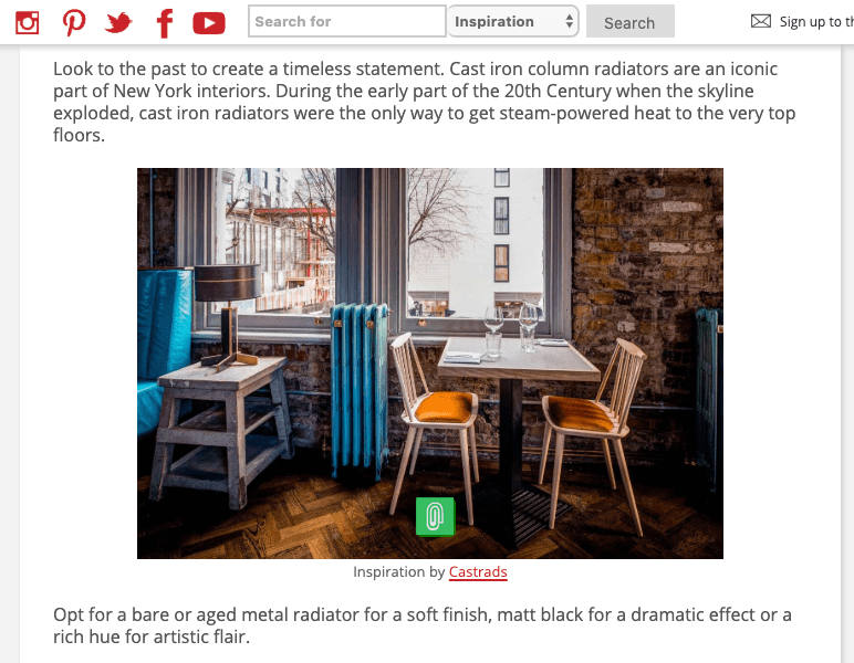 KBBArk Kitchens Bathroom Bedrooms, August 2018. Article about how to achieve the New York loft style in your home. Image of a Bronze verdigris cast iron radiator in a restaurant with mid century furniture and raw brick walls.