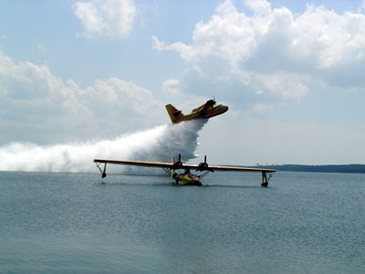 Dramatic photo of C-FNJF on the water at Biscarosse, France with a visiting Canadair CL-215 dropping its water load in the background Photo: Bernard Servieres