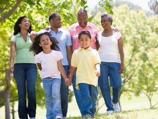 Extended family walking in park holding hands and smiling image