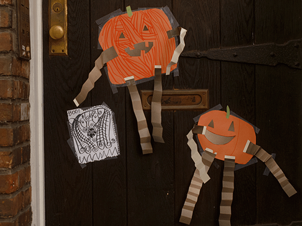 fall decorations with paper pumpkins who have long arms and legs taped on a door