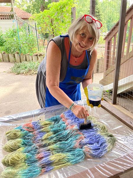 Pam applying dye to the yarn