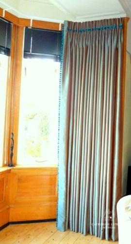 Full length grey silk interlined curtains in a Fife bay window