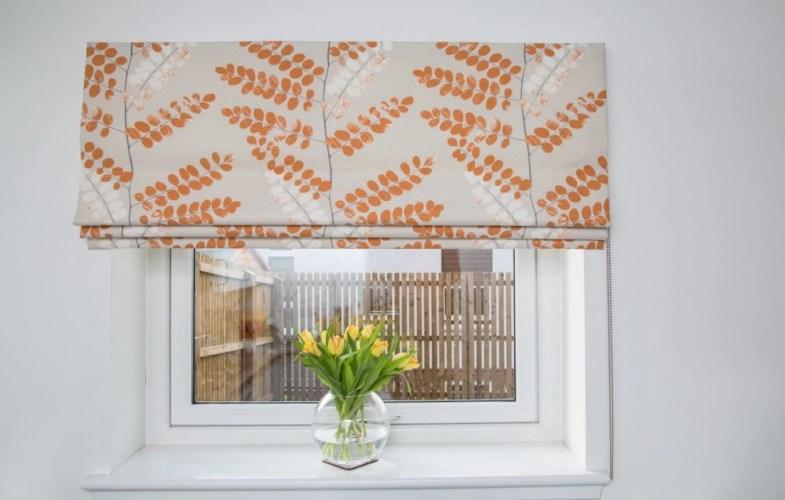 Hand sewn roman blind orange at an Edinburgh kitchen window