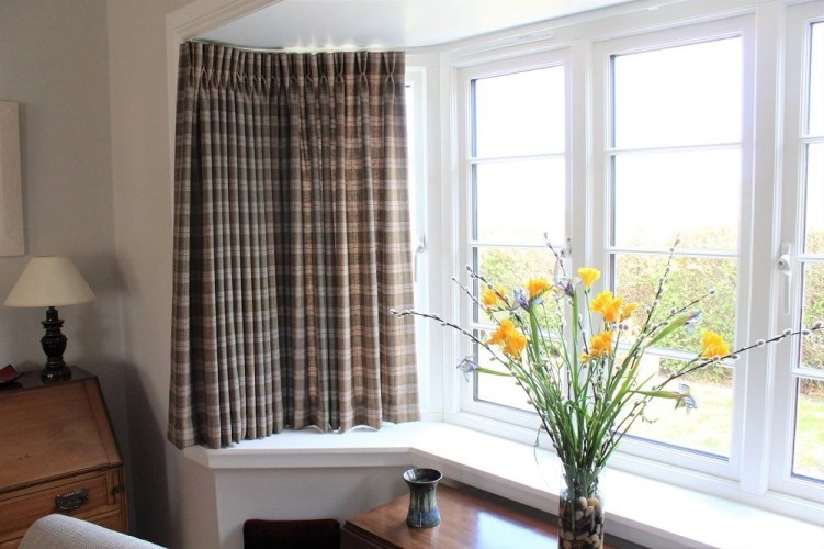 Made to measure wool plaid curtains hung on a curved track in a St Andrews living room