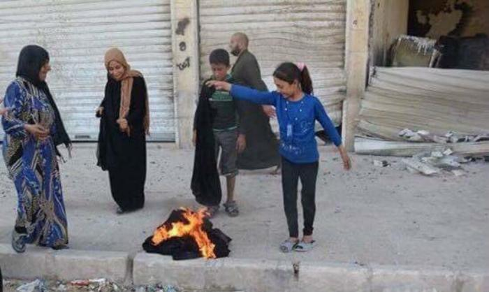 Women happy to be freed from the material burn their burkas.