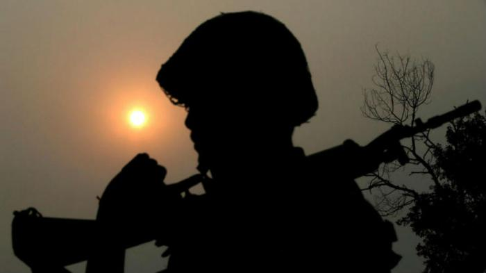 An Indian Border Security Force soldier is silhouetted against the sun as he patrols the border between India and Pakistan.