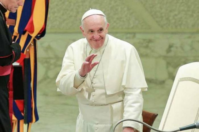 Pope Francis waves to pilgrims during.