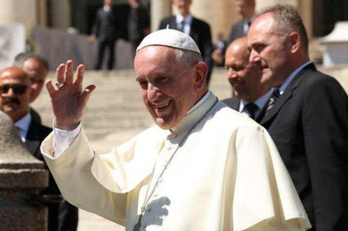 Pope Francis waves to pilgrims in St. Peter