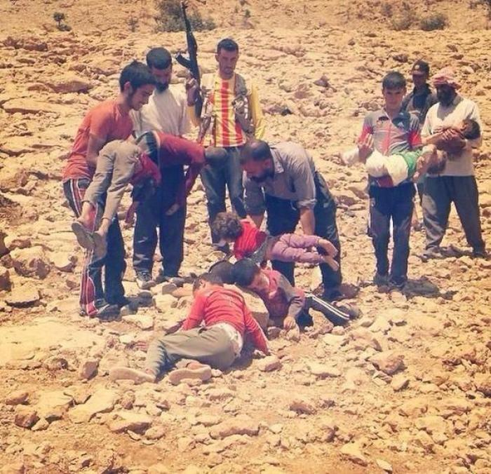 Kurdish men carry the bodies of children who died after being driven from their homes with nothing t