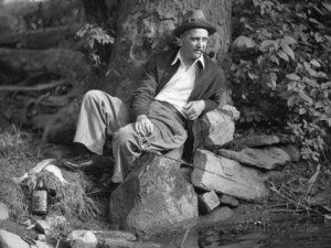george-marks-man-sitting-by-stream-fishing-while-smoking-pipe