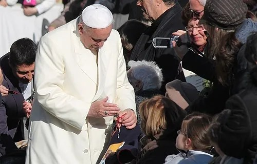 Pope Francis blesses a rosary for a pilgrim in St. Peter's Square during the Wednesday general audience on Dec. 4, 2013. Credit: Kyle Burkhart / CNA.