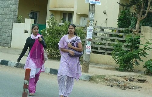 Young women walk along a street in Bangalore, India. Credit: Hillary Mast/CNA.