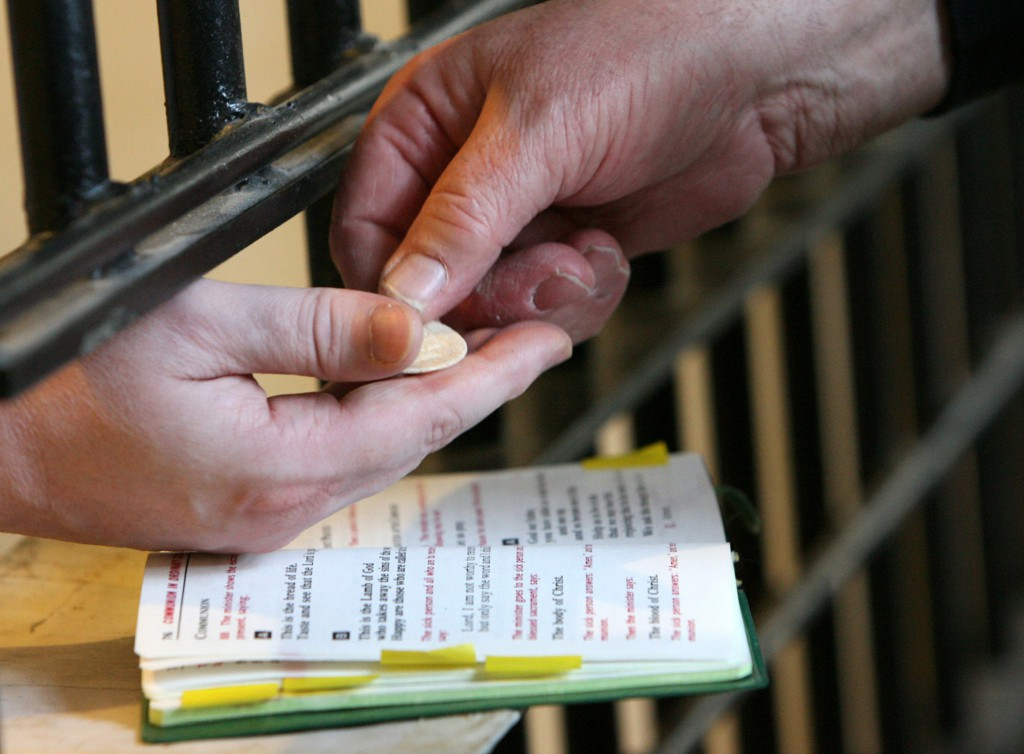 A deacon distributes Communion to a death-row inmate at Indiana State Prison in Michigan City, Ind. Father David Link of the Diocese of Gary, Ind., a prison chaplain, sees one-on-one relationships as a key to helping prisoners build healthy new lives. (CNS photo/Karen Callaway, Northwest Indiana Catholic)