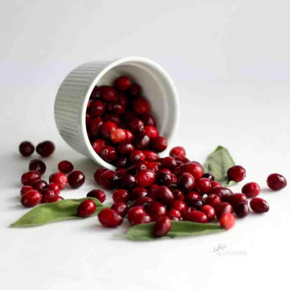 Fresh cranberries spilling from a ramekin - CathysGlutenFree.com