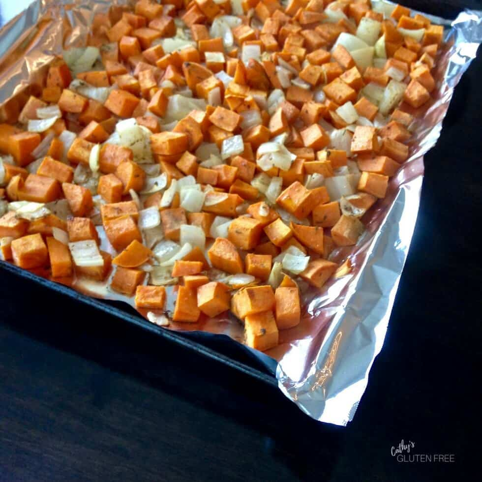 cubed sweet potatoes and onion roasting on a baking sheet