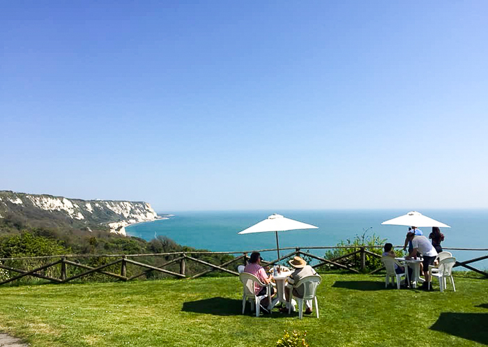 people at tables at Little Switzerland, Folkestone, overlooking the sea and cliffs