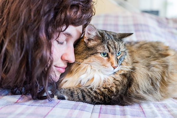 A woman resting and relaxing with an older cat.