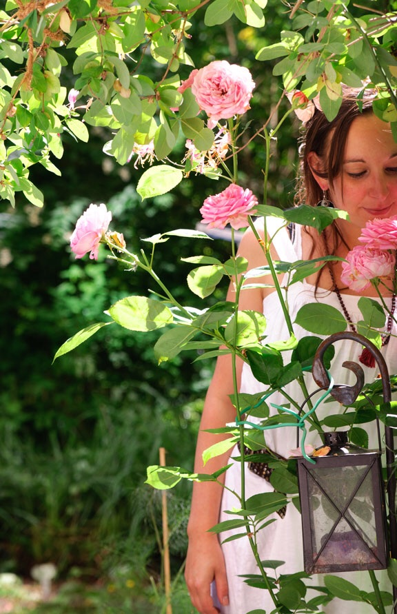 Girl in garden smelling roses
