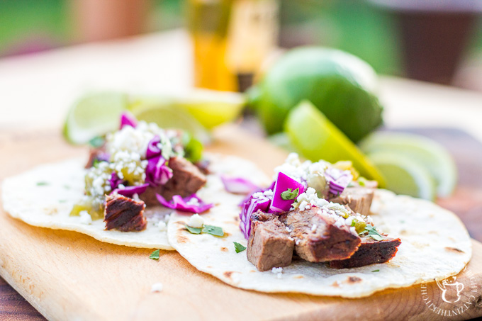 These steak street tacos are super tasty and incredibly easy to make! An inexpensive cut of steak works great, grilled alongside corn tortillas, with a fresh cabbage and salsa topping!