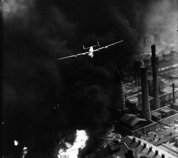 Liberator mal conseguindo escapar de Ploesti, antes de ser envolvido na nuvem de chamas e fumaça de um depósito de combustível incendiado.