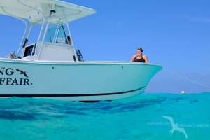 lady relaxing on the bow of our regulators 26fs private charter boat in grand cayman
