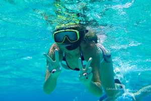 woman giving peace sign while snorkeling