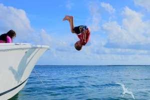boy doing a front flip from the boat at starfish point grand cayman