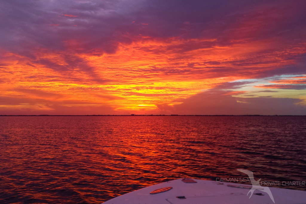 sunset from the boat with grand cayman behind on a sunset cruise