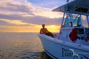 man relaxing on our charter boat with sunset behind