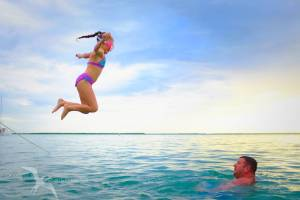 girl jumping from private charter boat to her dad at starfish point grand cayman