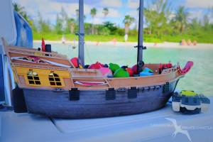 kids toy boat with starfish point grand cayman behind