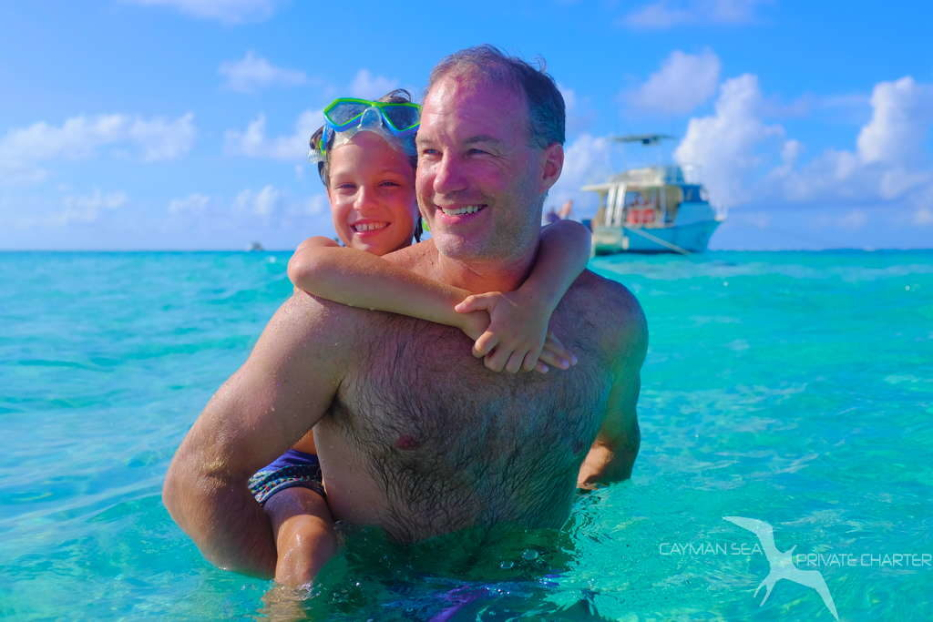 dad with son on his back having fun at stingray city grand cayman